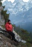 Caminante de reclinación de la montaña con la taza caliente de la bebida a disposición en el fondo nevoso de las montañas del inv fotos de archivo libres de regalías