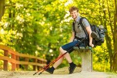 Caminante del hombre con la mochila que descansa sobre banco en rastro del bosque Foto de archivo libre de regalías