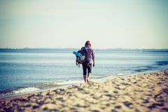 Caminante del hombre con la mochila que vagabundea por la playa Fotos de archivo