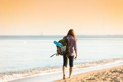 Caminante del hombre con la mochila que vagabundea por la playa Imagen de archivo libre de regalías