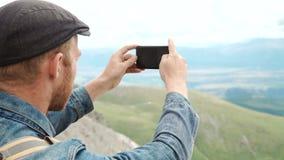 Caminante del hombre fuerte que toma la foto con el teléfono elegante en el pico de montaña Alba maravillosa almacen de metraje de vídeo