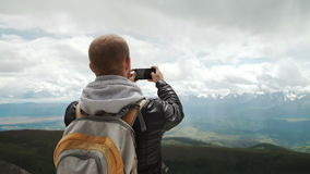 Caminante del hombre fuerte que toma la foto con el teléfono elegante en el pico de montaña Alba maravillosa metrajes