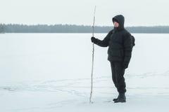 Caminante del invierno con el bastón del abedul que explora el llano escarchado nevoso Imagen de archivo libre de regalías