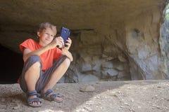 Caminante del muchacho que toma la imagen del paisaje de la montaña con el teléfono de la cámara de la cueva rocosa Fotos de archivo libres de regalías