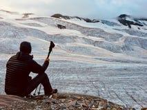 Caminante delante de un gran glaciar alpino Visión posterior Montaña italiana imagen de archivo