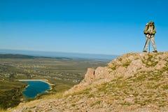 Caminante en cumbre de la montaña imagen de archivo libre de regalías