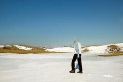Caminante en el campo de nieve del invierno Foto de archivo