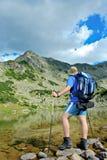 Caminante en el lago Prevalski en el parque nacional Pirin Foto de archivo libre de regalías