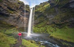 Caminante en la cascada de Kvernufoss imagenes de archivo