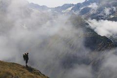 Caminante en la montaña con el bebé en el suyo detrás imagenes de archivo