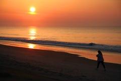 Caminante en la playa en la salida del sol Fotos de archivo