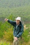 Caminante en montañas contra bosque verde Foto de archivo