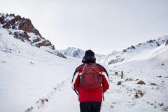 Caminante en montañas nevosas imagenes de archivo