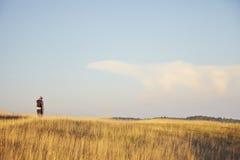 Caminante en prado de la montaña Imagen de archivo