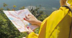 Caminante en un impermeable amarillo que mira el mapa del top de la montaña mujer con el mapa en las montañas 4k metrajes