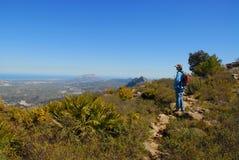 Caminante en una pista de la montaña, admirando la visión fotografía de archivo