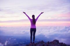 Caminante feliz de la mujer con los brazos abiertos en la puesta del sol en pico de montaña fotos de archivo