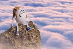 Caminante feliz del huevo de Pascua que se sienta en una montaña imagenes de archivo
