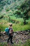 Caminante femenino con la mochila que camina abajo de la trayectoria cobbled al valle verde enorme de Paul Santo Antao Cape Verde Foto de archivo libre de regalías