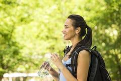 Caminante femenino con la mochila que camina en rastro del bosque del país Foto de archivo libre de regalías