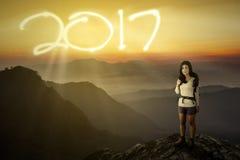 Caminante femenino en la montaña con los números 2017 Fotos de archivo libres de regalías