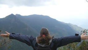 Caminante femenino joven con la mochila que alcanza encima del top de montaña y de manos aumentadas Situación turística de la muj almacen de video
