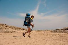 Caminante femenino joven que camina con los palillos en desierto imagenes de archivo