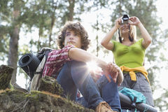 Caminante femenino joven que fotografía a través de la cámara digital mientras que hombre que mira lejos en bosque Imagen de archivo