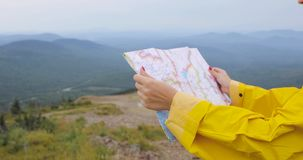 Caminante femenino joven que mira el mapa del top de la montaña almacen de video