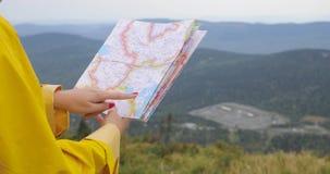 Caminante femenino joven que mira el mapa del top de la montaña almacen de metraje de vídeo