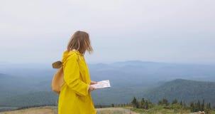Caminante femenino joven que mira el mapa del top de la montaña metrajes