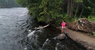 Caminante femenino que coloca el río cercano 4k almacen de video