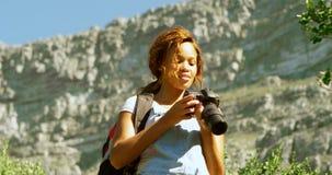 Caminante femenino que hace clic las fotos con la cámara digital 4k almacen de metraje de vídeo
