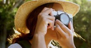 Caminante femenino que hace clic las fotos con la cámara 4k del vintage metrajes