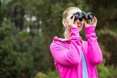 Caminante femenino que mira a través de los prismáticos Fotografía de archivo libre de regalías
