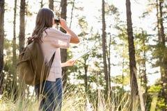 Caminante femenino que mira a través de los prismáticos Foto de archivo libre de regalías
