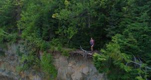 Caminante femenino que se coloca en el acantilado en el bosque 4k metrajes