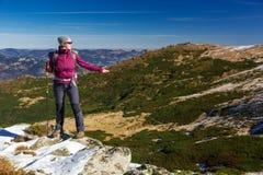 Caminante femenino que se coloca en las rocas nevosas que admiran el invierno escénico Mountain View Fotografía de archivo