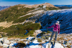 Caminante femenino que se coloca en las rocas nevosas que admiran el invierno escénico Mountain View Imagen de archivo