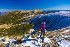 Caminante femenino que se coloca en las rocas nevosas que admiran el invierno escénico Mountain View Imagen de archivo libre de regalías