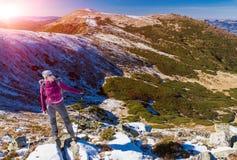 Caminante femenino que se coloca en las rocas nevosas que admiran el invierno escénico Mountain View Sun Foto de archivo libre de regalías