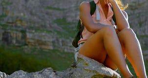 Caminante femenino que se relaja en roca en el campo 4k almacen de metraje de vídeo