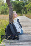 Caminante femenino que se sienta en la trayectoria de madera en naturaleza Foto de archivo libre de regalías