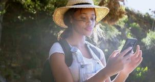 Caminante femenino que usa el teléfono móvil en el campo 4k almacen de video