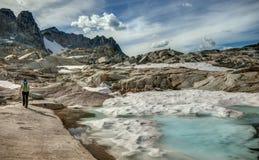 Caminante femenino Rocky y lavabo alpino Nevado Foto de archivo
