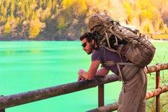Caminante joven que mira un lago de la montaña Fotografía de archivo