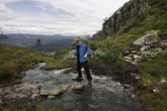 Caminante joven que salta sobre el río de la montaña Fotos de archivo