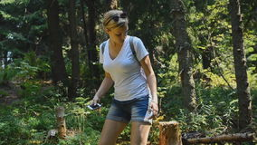 Caminante joven que usa el teléfono elegante en el bosque