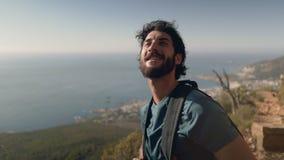 Caminante masculino con la mochila que mira el mar contra el cielo almacen de metraje de vídeo