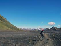 Caminante masculino experimentado que camina solamente en el salvaje con la mochila pesada en el desierto negro, pista de senderi imagenes de archivo